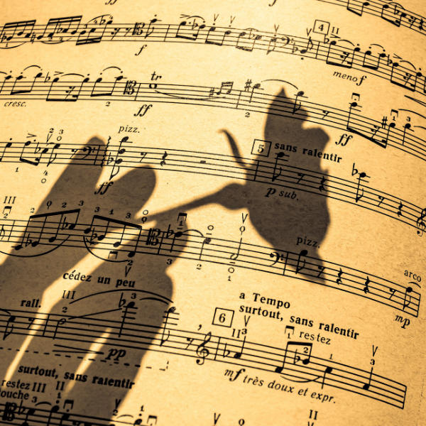 Shadow of hand holding rose on sheet music